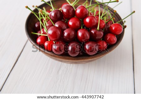 Sweet fresh cherries in bowl closeup at wooden background. Juicy fruits on white rustic wood table. Healthy organic food. - stock photo