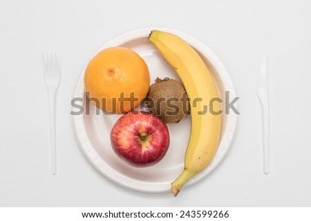 Sweet fresh fruits on plate isolated on white - stock photo