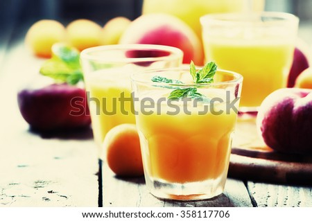 Sweet fresh peach juice with ice, selective focus and toned image
