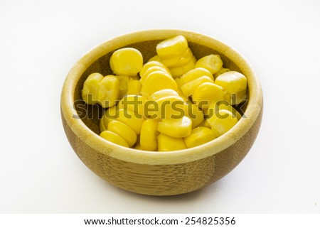 Sweet, fresh, raw, ripe, juicy  kernels of corn in wood bowl on the white background. - stock photo