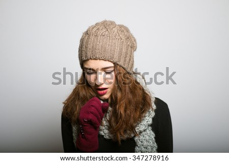Sweet girl fell ill and coughing, winter Christmas and New Year concept isolated studio shot on a gray background - stock photo