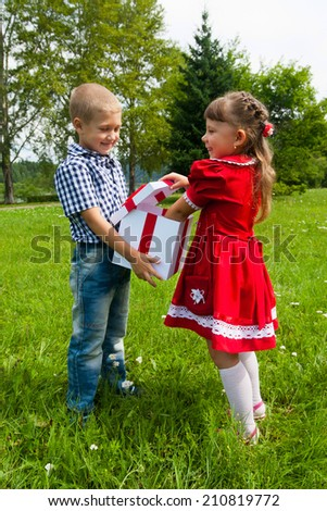 Sweet  Girl Gives Her  Brother A Wrapped Gift on a Picnic Blanket Outdoors at the Park. - stock photo