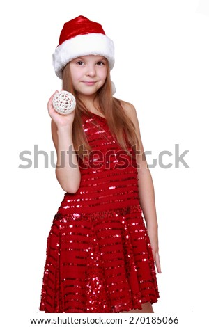 Sweet girl in Santa hat holding Christmas decoration in hands - stock photo