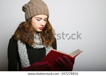 Sweet girl reading a book, Christmas and New Year winter concept isolated studio shot on a gray background - stock photo