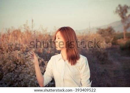 sweet girl, sweet young girl playing in grass field with sun light - stock photo