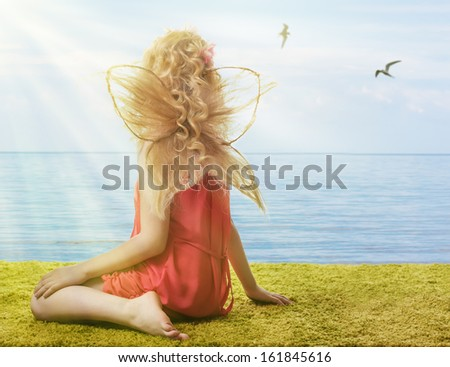 Sweet girl with butterfly wings on the beach. - stock photo