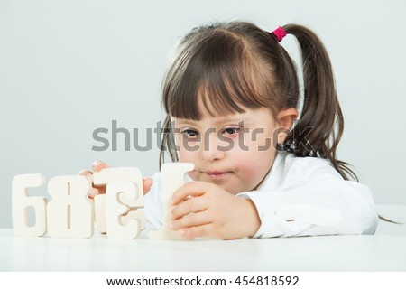 Sweet girl with Down Syndrome, playing with wooden numbers - stock photo