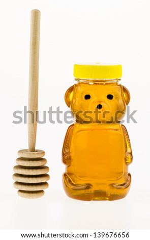 Sweet golden honey in a plastic bear shaped container with a wooden honey dipper. - stock photo