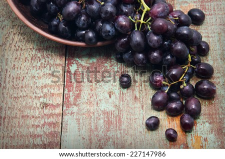 sweet grapes in basket wooden background - stock photo