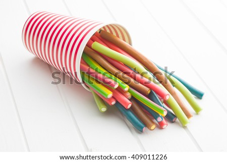 Sweet gummy sticks with different flavor. Tasty candies in paper cup. - stock photo