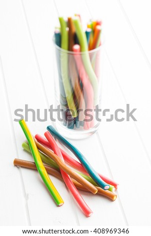 Sweet gummy sticks with different flavor. Tasty candies isolated on white table. - stock photo