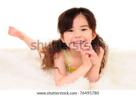 sweet happy little asian girl on a White blanket - stock photo