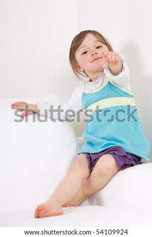 sweet happy little girl on sofa - stock photo