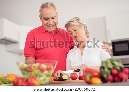 Sweet Happy Middle Aged Couple Preparing Healthy Fresh Vegetable Salad for Dinner at the Kitchen - stock photo