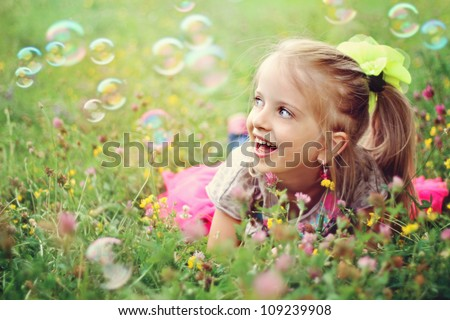 Sweet, happy, smiling six year old girl laying on a grass in a park playing with bubbles and laughing