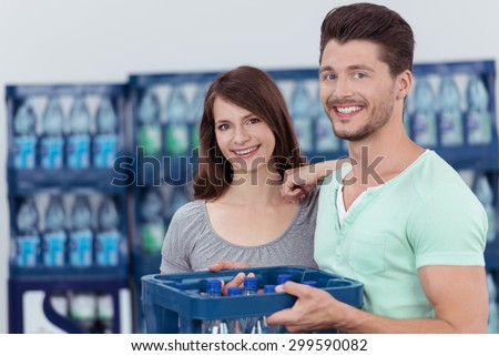 Sweet Happy Young Couple with a Case of Bottled Water Inside the Store, Smiling at the Camera. - stock photo