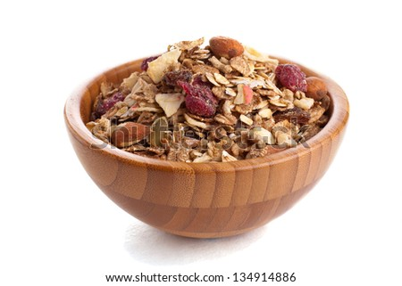 Sweet healthy muesli in a wooden bowl over white - stock photo