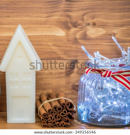 Sweet Home Concept with Different Cute Xmas Things on the Wooden Shelf, such as White Candle House, Xmas Lights in the Glass Jar, and Cinnamon Sticks