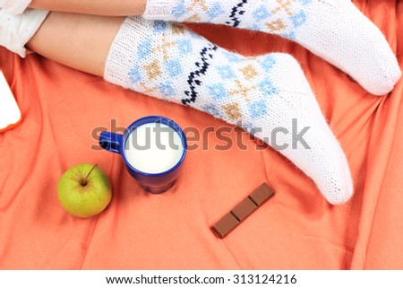 Sweet home or Cozy home background, Knitted socks, Knitted background, Healthy lifestyle, Drinking milk, Milk and chocolate, Sweet November, Bed and breakfast, At home on laptop, White knitted socks - stock photo