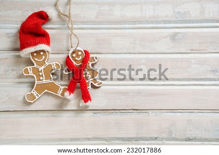 sweet homemade cookies in funny Santa hat for Christmas on white old wooden background, holiday concept - stock photo