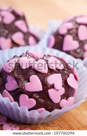 sweet homemade dark chocolate pralines with pink hearts - stock photo