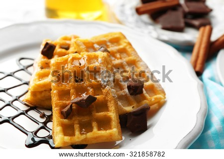 Sweet homemade waffles with chocolate sauce on plate, on light background