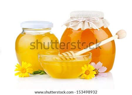 Sweet honey in glass jars with flowers and dipper isolated on white background  - stock photo