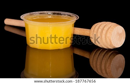 Sweet honey in jar with honey dipper isolated on black - stock photo