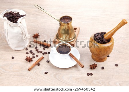 sweet hot drink : black arabic coffee in small white cup with mortar and pestle , bag full beans, copper old style cezve , decorated with cinnamon sticks and anise stars - stock photo