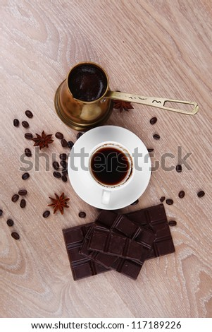 sweet hot drink : black coffee in small white cup with beans on a wooden table with stripes of dark chocolate and copper cezve