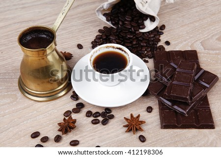 sweet hot drink : black Turkish coffee in small white mug with coffee beans spilled on a wooden table with stripes of dark chocolate and copper Arab Cezve full coffee - stock photo