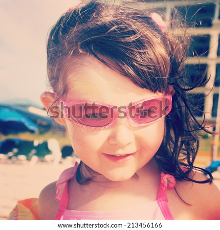 sweet instagram closeup of little girl at the beach wearing sunglasses - stock photo