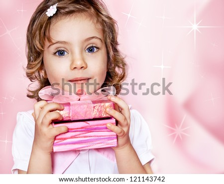 Sweet kid holding gift wrapped in pink paper - stock photo