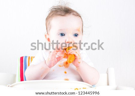 Sweet little baby eating a carrot in a white high chair