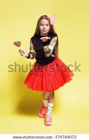 Sweet little blonde girl in red skirt, sneakers, sweatshirt holding a lolly pop. Kid fashion photo. Long hair style - stock photo