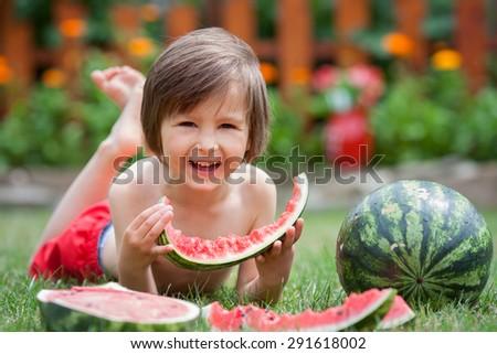 Sweet little boy, eating watermelon in the garden, summertime - stock photo