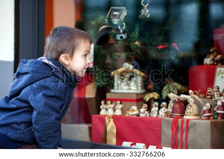 Sweet little boy, looking through a window in shop, decorated for Christmas holidays - stock photo