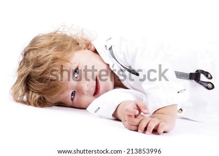 Sweet little boy lying on the floor - stock photo