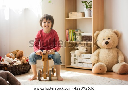 Sweet little boy, preschool child, playing at home with wooden horse, childhood games - stock photo