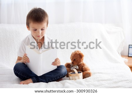Sweet little boy, reading a book in bed and eating blueberries, teddy bear next to him on the bed