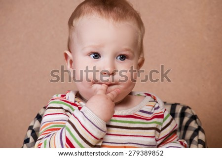 Sweet little boy sitting with finger in the mouth - stock photo