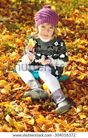 sweet little girl eating apple outdoors in fall time - stock photo