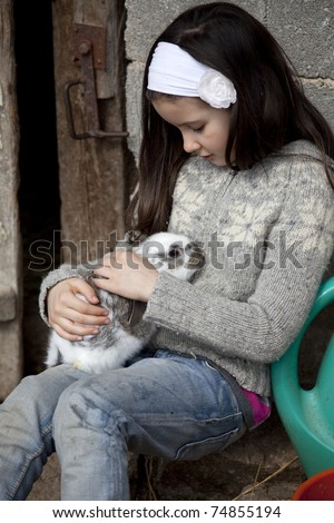 Sweet little girl hugs baby rabbit in the farm - stock photo