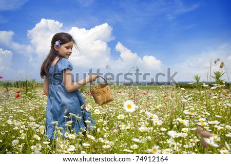 Sweet little girl in a meadow with wild spring flowers - stock photo
