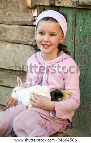 Sweet little girl in the farm play with her rabbit - stock photo