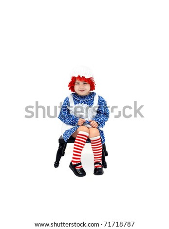 Sweet little girl is dressed as a rag doll.  She is grinning mischieviously and sitting on a black milking stool.