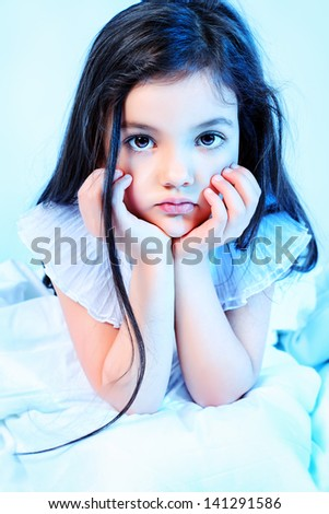 Sweet little girl is going to sleep in a bed. - stock photo