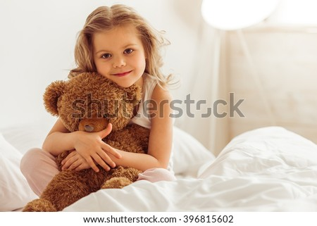 Sweet little girl is hugging a teddy bear, looking at camera and smiling while sitting on her bed at home - stock photo