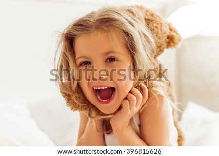 Sweet little girl is playing with a teddy bear and smiling while sitting on her bed at home, close up - stock photo
