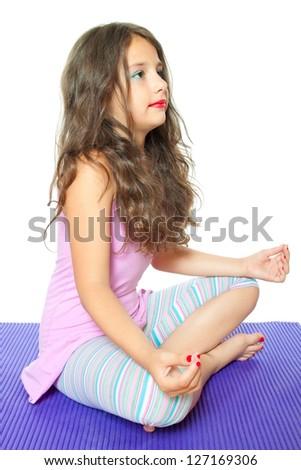 sweet little girl meditating isolated on white - stock photo